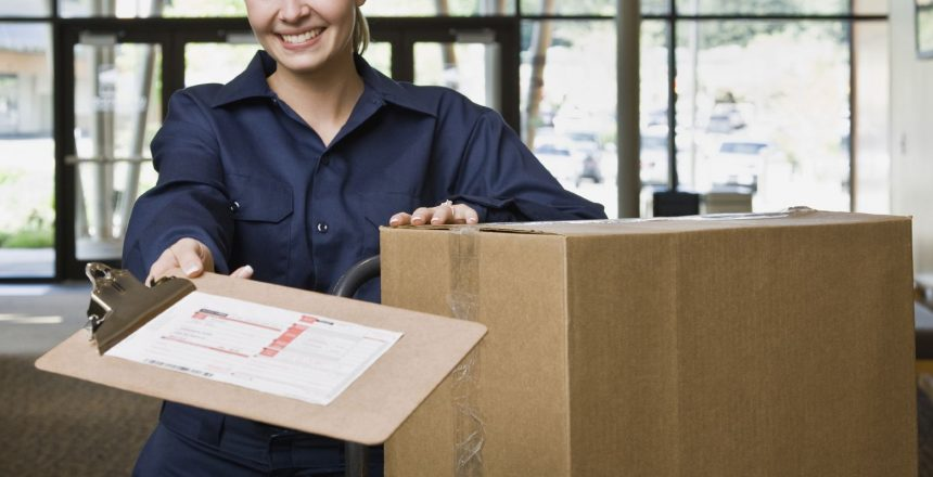 Friendly delivery woman in uniform with stack of cardboard boxes